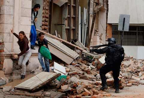 военный пытается остановить мародеров в Чили